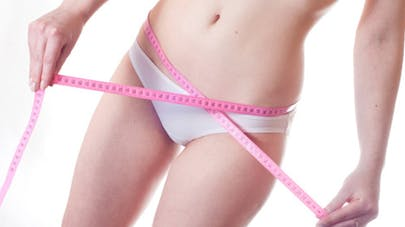 femme mesure sa taille pour connaitre son poids