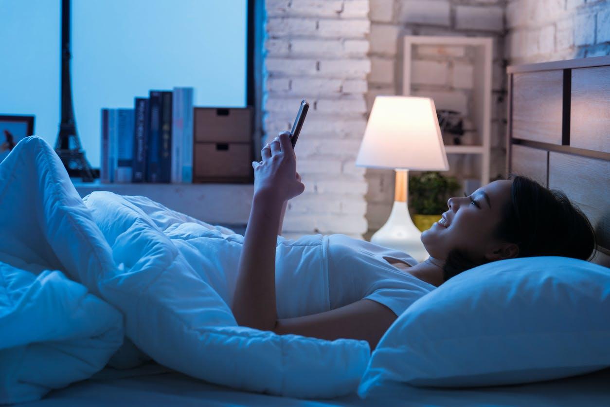 femme et portable au lit