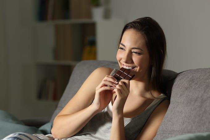 jeune femme qui mange une tablette de chocolat