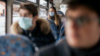 Des personnes dans un bus qui portent un masque de protection.