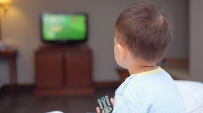 Un enfant qui tient une télécommande dans la main et regarde la télévision.