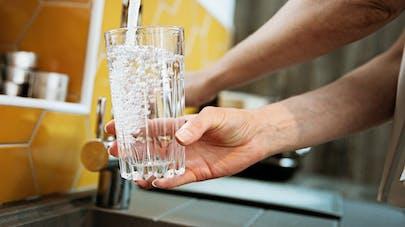 Une personne positionne un verre sous le robinet pour le remplir.