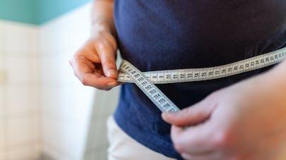 Une personne se mesure le tour de taille.