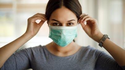 Une femme porte un masque de protection jetable contre le coronavirus.