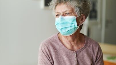Une femme âgée porte un masque de protection.