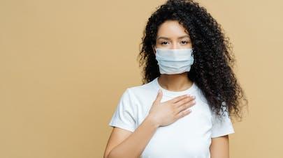 Une femme avec un masque de protection place sa main sur sa poitrine.