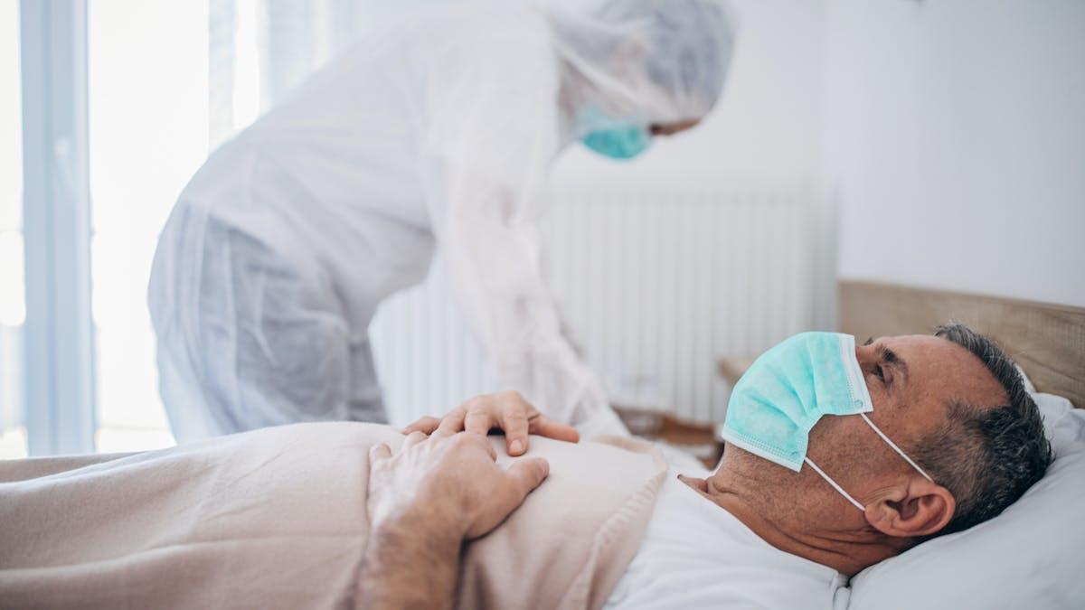 Un homme atteint par la Covid-19 allongé dans une chambre d'hôpital.