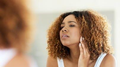 Nouveaux symptôme coronavirus : une femme se regarde dans un miroir.