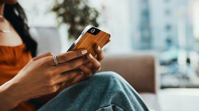 Une jeune femme avec un smartphone dans la main.