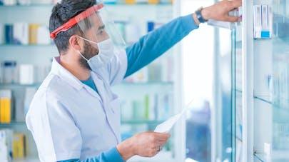 Un pharmacien avec une visière et un masque.