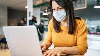 Une personne avec un masque utilise un ordinateur