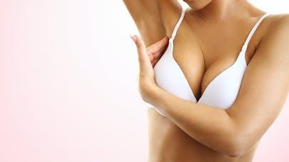 Une femme en soutien-gorge à la recherche d'une boule dans son sein.