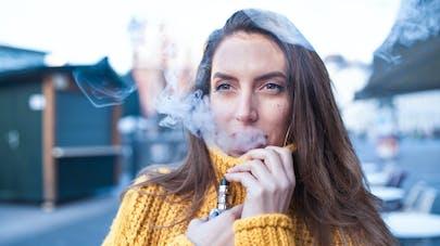 Une femme qui utilise sa cigarette électronique.