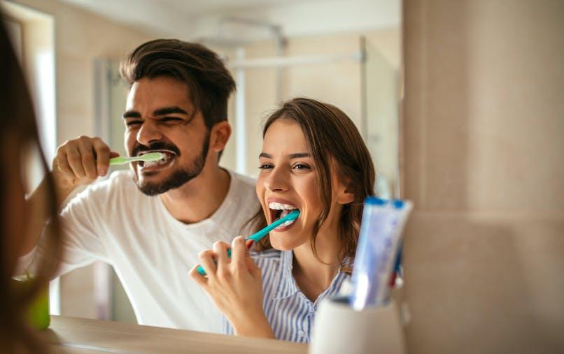 homme et femme se brossant les dents