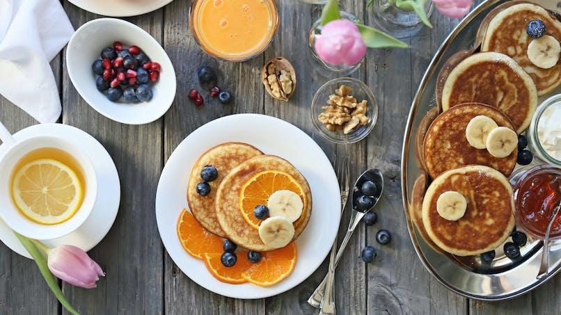 Un brunch d'été avec des pancakes, des fruits, du jus d'orange.