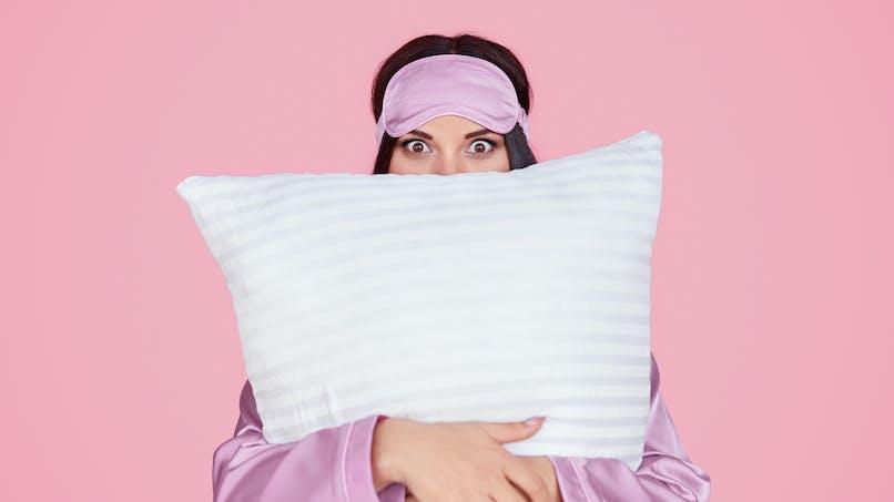 Une femme avec un oreiller dans les bras.