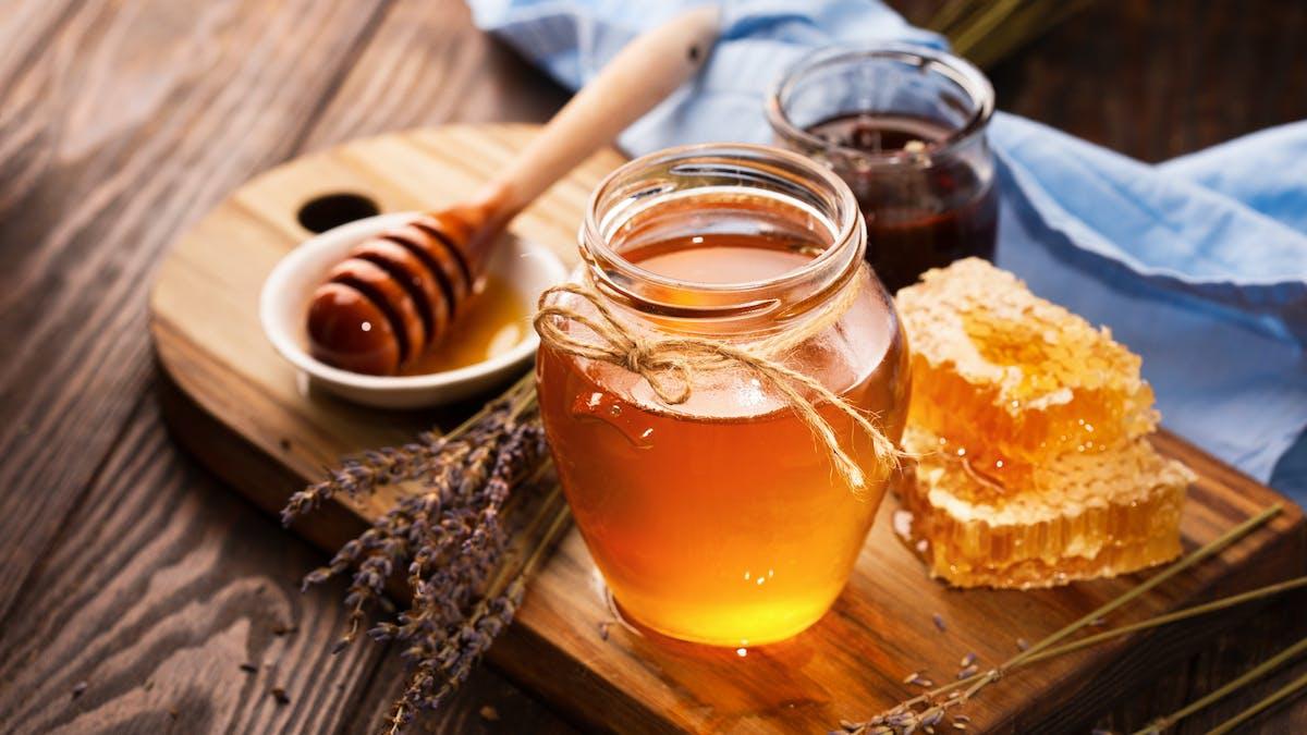 Des pots de miel déposés sur une planche en bois