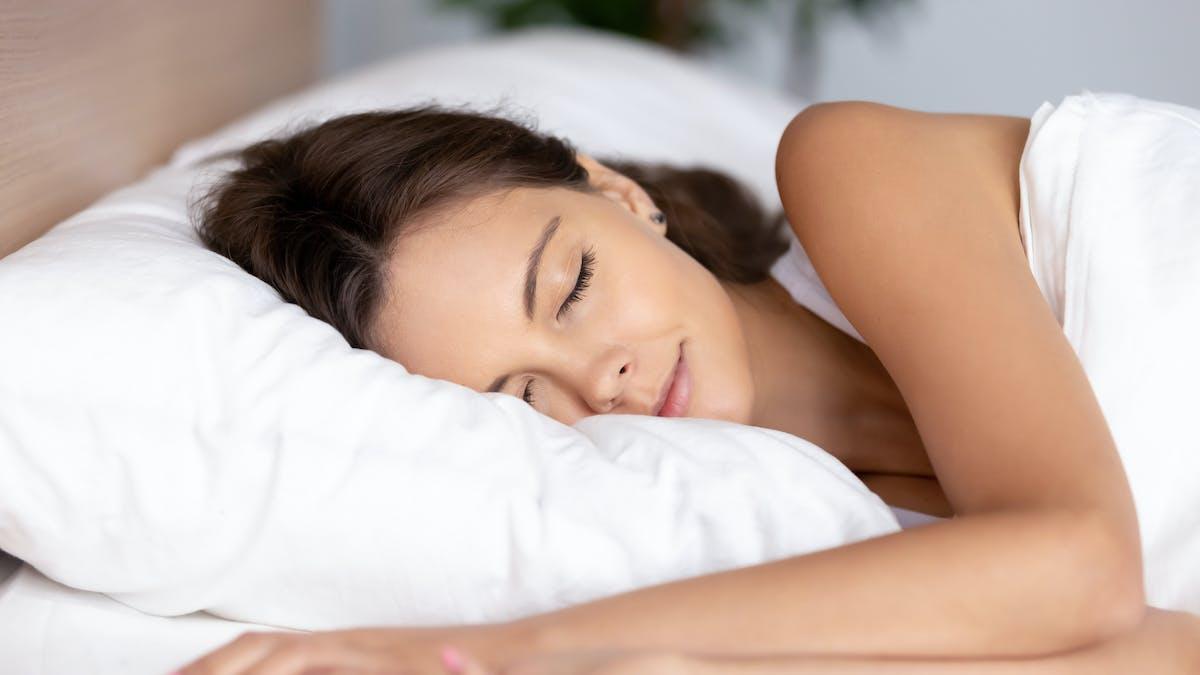 Une femme dort sur un oreiller