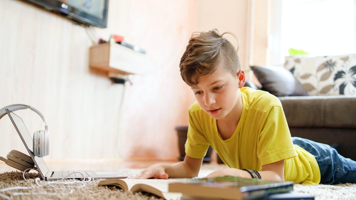 Enfant lisant à la maison.