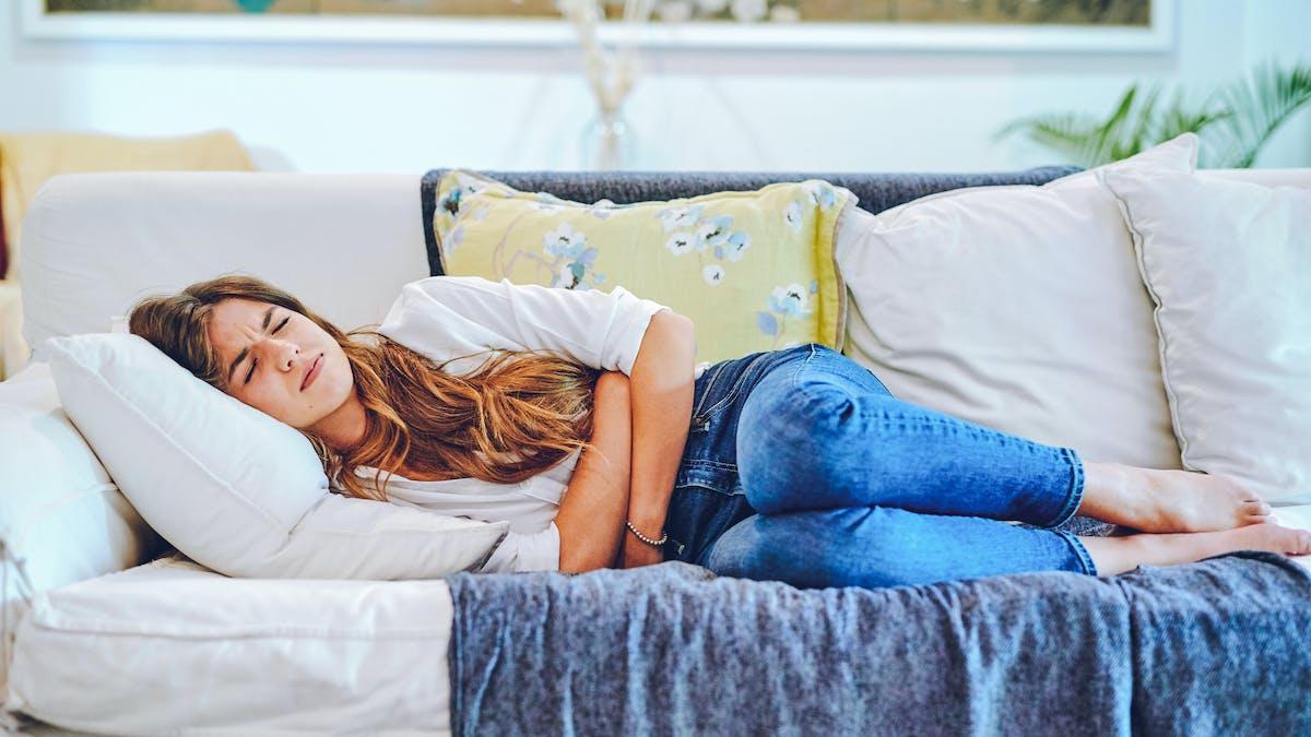 Une femme allongée sur le canapé souffre de douleurs au ventre