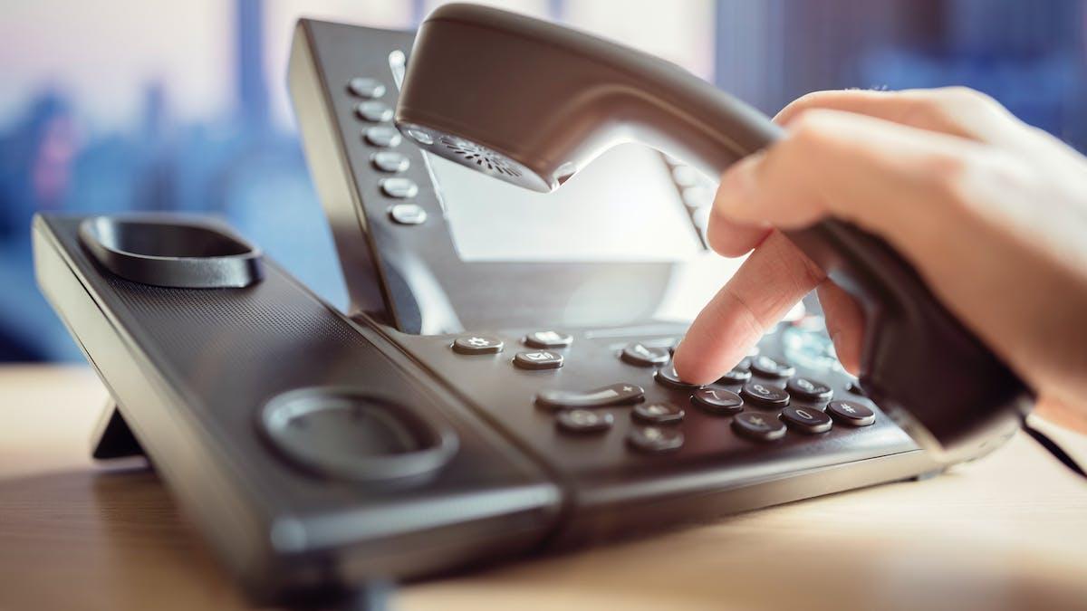 Une personne compose un numéro de téléphone